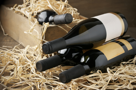 Assorted closed wine bottles lying on straw and vintage wooden box.