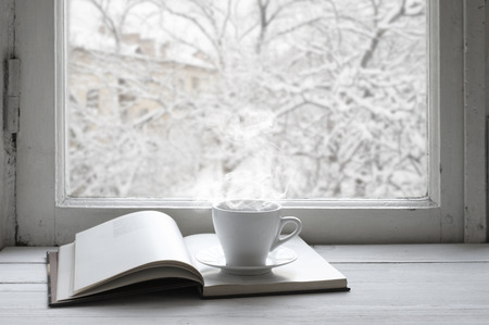 Cozy winter still life: cup of hot coffee and opened book on vintage windowsill against snow landscape from outside.