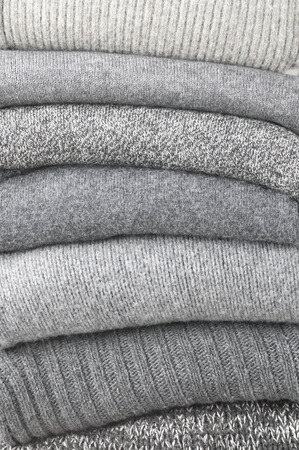tricot: Stack of gray woolen knitted sweaters close-up. Stock Photo