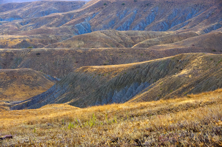 flexure: Pictorial landscape: colorful hills of blue clay with dry grass in rainy weather. Meganom cape, Crimea. Stock Photo