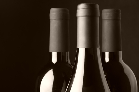wine store: Three assorted wine bottles close-up on black background. Monochrome sepia toned image. Focus on front bottle.