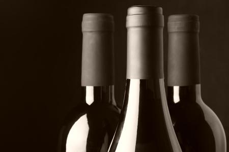wine bottle: Three assorted wine bottles close-up on black background. Monochrome sepia toned image. Focus on front bottle.