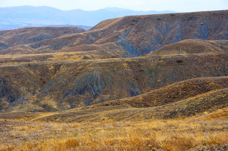 pictorial: Pictorial landscape: colorful hills of blue clay with dry grass in rainy weather. Meganom cape, Crimea. Stock Photo