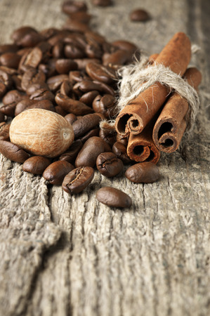seeds coffee: Pile of coffee beans, cinnamon sticks and nutmeg on old wood. Stock Photo