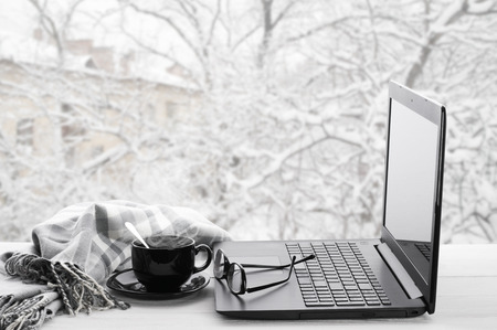 Cozy winter still life: laptop, glasses, cup of hot coffee and warm plaid on windowsill against snow landscape from outside.