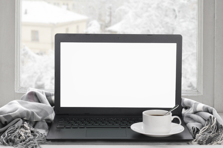 Cozy winter still life: laptop with blank screen, cup of coffee and warm plaid on windowsill against snow landscape from outside.