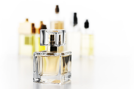 Various woman perfumes set on white background. Selective focus on front bottle Archivio Fotografico