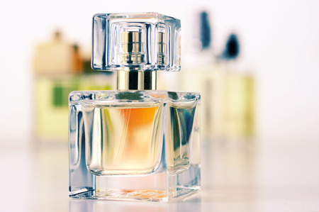 Various woman perfumes set on light background. Selective focus on front bottle