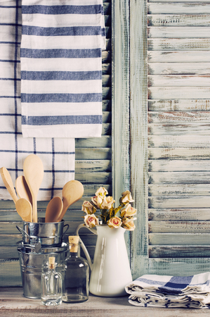 Rustic kitchen still life: white jug with roses bunch, galvanized buckets with wooden spoons, glass bottles and linen towels against vintage wooden shutters. Foto de archivo