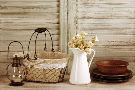 domestic kitchen: Rustic kitchen still life: wire basket, jug with roses bunch, ceramic dishware and lantern against vintage wooden shutters. Filtered toned image.