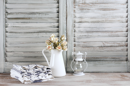 Rustic kitchen still life: white jug with roses bunch, towels stack and lantern against vintage wooden shutters. Stock Photo