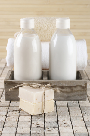 shower gel: Set of bathroom accessory on stone tile: soaps, shower gel, lotion, towel, loofah.