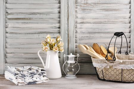 rustic kitchen: Rustic kitchen still life: wire basket with wooden spoons, jug with roses bunch, towels stack and lantern against vintage wooden shutters.