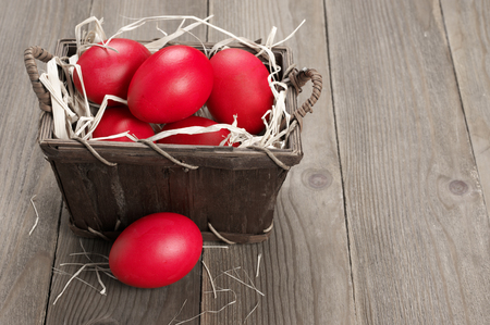 Traditional red Easter eggs in basket on wood background.