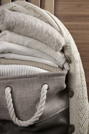 knitwear: Stack of warm white knitwear in fabric basket close-up on wooden background. Stock Photo