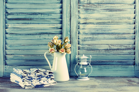 Rustic kitchen still life: white jug with roses bunch, towels stack and lantern against vintage wooden shutters. Filtered toned image.