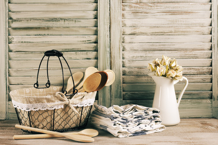 Rustic kitchen still life: wire basket, jug with roses bunch and towels stack against vintage wooden shutters. Filtered toned image.