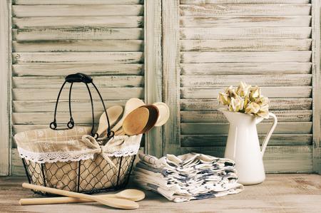 Rustique cuisine toujours la vie: panier métallique, pichet avec des roses tas et serviettes stack contre des volets en bois d'époque. Filtré image de toner. Banque d'images