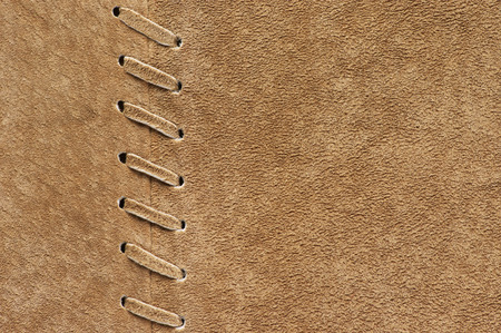 suede: Natural tan color suede texture with decorative stitch as background.