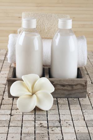 soap: Set of bathroom accessory on stone tile: frangipani-shaped soap, shower gel, lotion, towel, loofah.