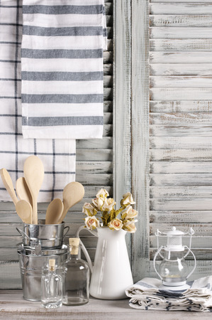 country house style: Rustic kitchen still life: white jug with roses bunch, galvanized buckets with wooden spoons, glass bottles, lantern and linen towels against vintage wooden shutters. Stock Photo