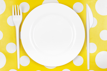 bar tool set: Disposable tableware set: white plate with plastic fork and knife on bright yellow polka dot background. Top view point.