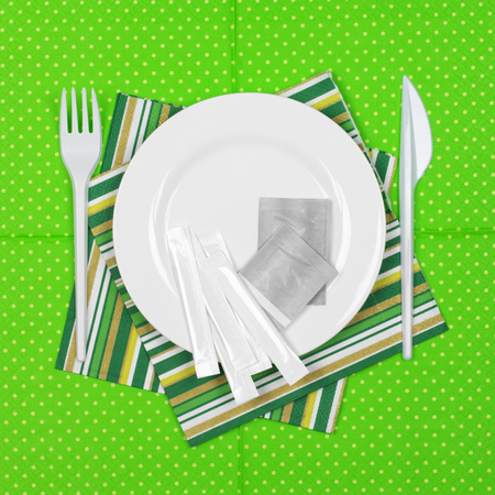 bar ware: Disposable fast food set: white plate with packed toothpicks and condiment bags and plastic cutlery on bright green polka dot paper napkin. Top view point.