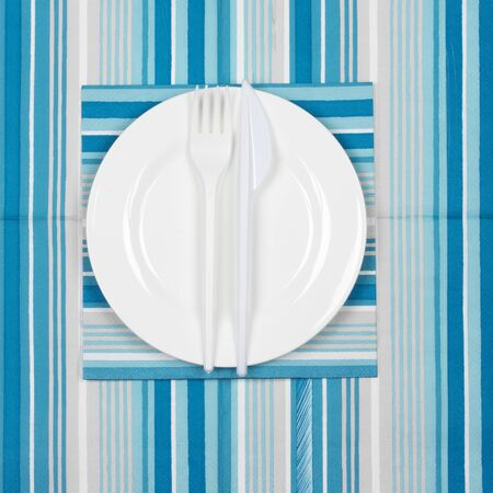 bar ware: Disposable tableware set: white plate with plastic fork and knife on blue striped paper napkins. Top view point.
