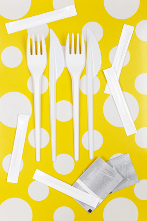 bar tool set: Disposable fast food set: white plastic forks and knifes with packed toothpicks and condiment bags on bright yellow polka dot background. Top view point.