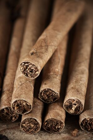aromatic: Aromatic cigars pile on vintage wood close-up. Stock Photo