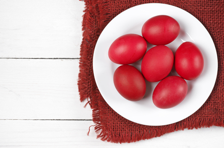 Traditional red Easter eggs in plate with napkin on white wood background. Top view point.