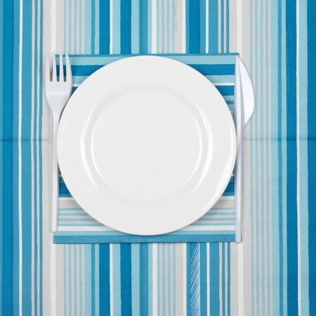 bar tool set: Disposable tableware set: white plate with plastic fork and knife on blue striped paper napkins. Top view point.