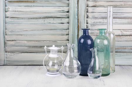 Les bouteilles vides colorés en verre et lanterne contre des volets en bois vintage.