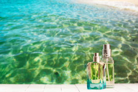 Two summer perfumes on white wooden table against defocused sea water.
