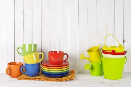 colorful still life: Kitchen still life: stack of colorful dishware and buckets against rustic white wood wall.