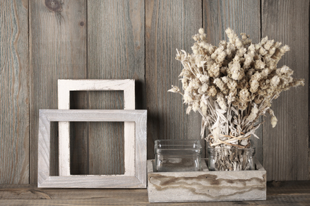 Rustic kitchen still life: dried flowers bunch and wood fotoframes against vintage wooden background. Stock Photo