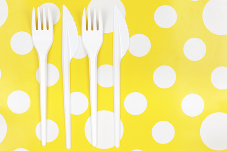 bright color: Disposable cutlery: white plastic forks and knifes on bright yellow polka dot background. Top view point.