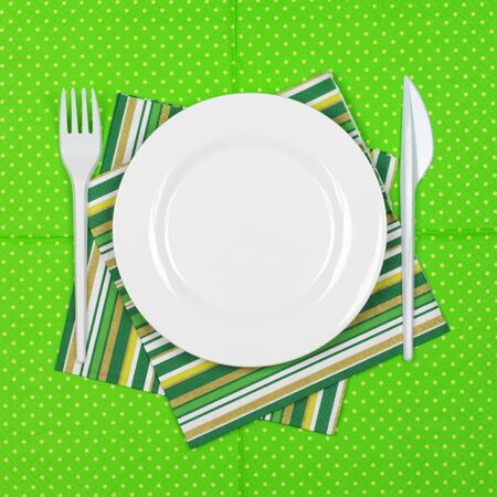 bar ware: Disposable tableware set: white plate with plastic fork and knife on bright green polka dot paper napkin. Top view point.