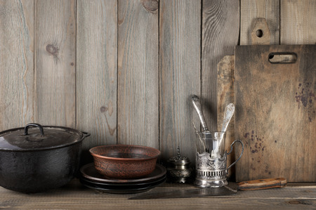 Vintage rustic kitchen still life: silver glass holder with cutlery, ceramic dishware, cast iron cauldron and cutting boards against vintage wooden background.