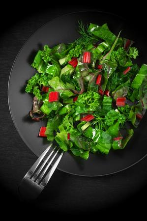 lechuga: Primavera vitamina ensalada fresca de lechuga, acelga, tatsoi, cebolleta, perejil y eneldo en un plato negro con un tenedor en la madera negro. Punto de vista superior.