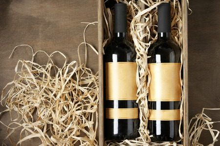 drink bottle: Two closed wine bottles lying on straw in vintage wooden box on wood background. Top view point.