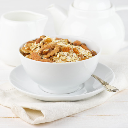 high key: Dry oatmeal flakes with walnuts, almonds and raisins in white bowl against white dishware. High key. Shallow DOF. Stock Photo