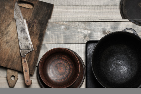 Vintage kitchen cooking utensils on rough wooden background: cutting boards, knife, crockery and cast iron cauldron. Top view point.