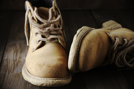 durability: Old shabby leather hiking boots close-up on wooden background.