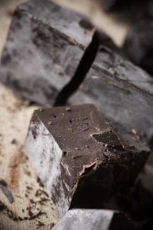 graining: Broken dark bitter chocolate chunk close-up on wooden board.