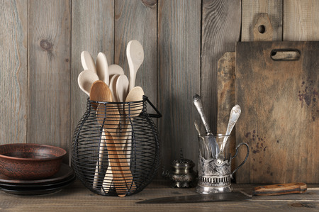 Vintage rustic kitchen still life: silver glass holder with cutlery, ceramic dishware, wire basket with wood spoons and cutting boards against vintage wooden background. Stockfoto