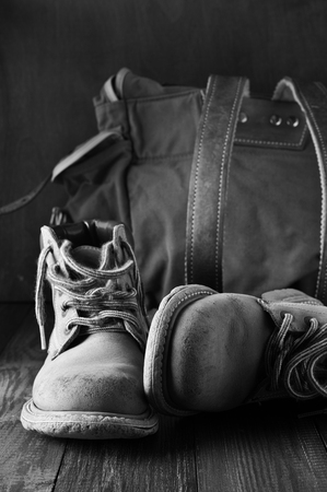 outworn: Old shabby leather hiking boots and backpack on wooden background. Monochrome black and white image. Stock Photo