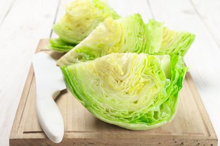 Cortar trozos de lechuga iceberg con un cuchillo de cocina a bordo de corte.