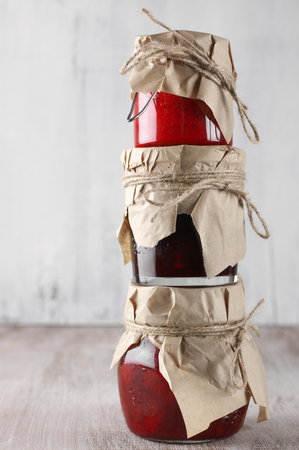 glass paper: Stack of assorted jams in glass jars on rustic wooden background.