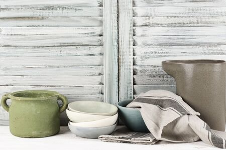 rustic kitchen: Simple rustic kitchen still life: rough ceramic pot, bowls, jug and towel against shabby wooden shutters. Stock Photo